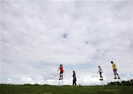 A coach and youth walk on stilts at Circus Smirkus camp in Craftsbury Common, Vermont August 5, 2008. REUTERS/Brian Snyder