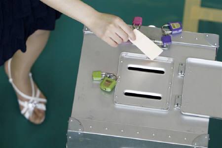 7月13日、麻生首相が衆院を21日ごろに解散し、8月30日に衆院選の投開票日を設定する日程を決断したことを明らかに。。写真は12日、東京都議会選挙で投票する女性(2009年 ロイター/Yuriko Nakao)