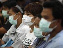 <p>Pessoas com máscara para se proteger do vírus da gripe H1N1 na Tailândia. 13/07/2009. REUTERS/Chaiwat Subprasom</p>