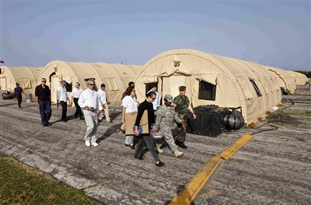 In this photo, reviewed by the U.S. military, a Pentagon official and military personnel escort a group of journalists with no cameras or recording materials to a court hearing for the five September 11, 2001 attack co-defendants, at Camp Justice, the site of the U.S. war crimes tribunal compound, at Guantanamo Bay U.S. Naval Base, July 16, 2009. REUTERS/Brennan Linsley/Pool