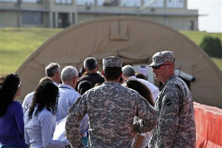In this photo, reviewed by the U.S. Military, military personnel (foreground) escort a group of journalists with no cameras or recording materials to a court hearing for the five September 11, 2001 attack co-defendants, at Camp Justice, the site of the U.S. war crimes tribunal compound, at Guantanamo Bay U.S. Naval Base, July 16, 2009. REUTERS/Brennan Linsley/Pool