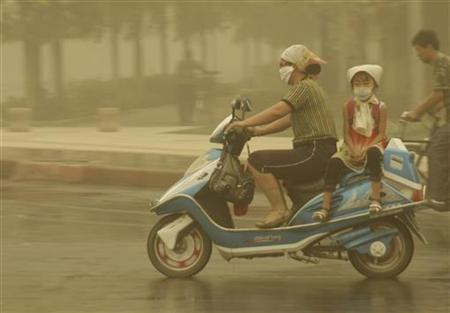 People ride amid sandstorms in Turpan, Xinjiang Uygur Autonomous Region May 26, 2009. REUTERS/China Daily