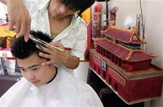 <p>Chinese hairdresser Huang Xin (R) cuts the hair of a customer in front of replicas of the Tiananmen Gate and Olympic torches that he made from human hair at his barbershop in Beijing August 3, 2009. H REUTERS/David Gray</p>