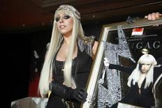 <p>U.S. singer Lady GaGa poses with a plaque presented to her by Universal Music Group during a media event for the launch of Singtel's AMPed music service in Singapore June 14, 2009. REUTERS/Tim Chong</p>