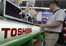 <p>Foto de archivo de un hombre mirando artículos de la compañía Toshiba en una tienda en Tokio, 29 jul 2009. La japonesa Toshiba dijo el lunes que se uniría a la Blu-ray Disc Association, su antigua adversaria, con el objetivo de fabricar reproductores blu-ray a finales del año para cubrir la demanda de video de alta definición. REUTERS/Yuriko Nakao</p>