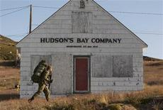 <p>A Canadian soldier passes by an old Hudson's Bay trading post after landing on a beach in Apex, Nunavut on Baffin Island in the Canadian Arctic August 18, 2009. REUTERS/Andy Clark</p>