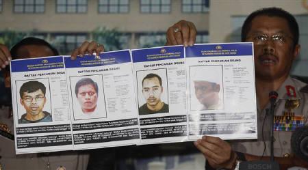 8月20日、インドネシアの武装勢力がオバマ米大統領の狙撃を計画。写真は指名手配された武装勢力メンバーの写真を公表するインドネシア警察スポークスマン。ジャカルタで19日撮影(2009年 ロイター/Dadang Tri)