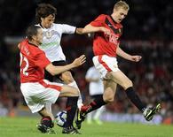 <p>Foto de arquivo de amistoso entre o Valência e o Manchester United mostra o espanhol David Silva brigando pela bola com os ingleses John O'Shea (à esquerda) and Darren Fletcher. REUTERS/Nigel Roddis</p>