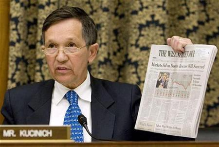 Rep. Dennis Kucinich (D-Ohio) holds up today's Wall Street Journal at the U.S. House Oversight and Government Reform Committee hearing on the cause and effects of the AIG bailout on Capitol Hill, October 7, 2008. REUTERS/Larry Downing