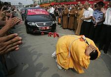 <p>Zhang Tingting, 52, pulls cars with her hair during a performance in Kaifeng, Henan province August 25, 2009. REUTERS/Stringer</p>