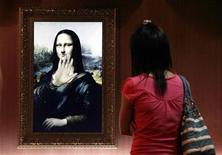 """<p>A visitor looks at a three-dimensional, holographic version of the 16th century portrait """"Mona Lisa"""" by Leonardo da Vinci as it waves to her in Beijing's Alive Gallery August 21, 2009. Known as the world's most famous painting, this holographic version moves and answers questions put to it by onlookers, and is one of several classical paintings showcased in an exhibition promoted as bringing """"the world's most famous artworks alive"""". REUTERS/David Gray</p>"""
