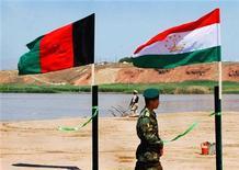 """<p>Солдат национальной армии Афганистана проходит мимо флагов Афганистана(слева) и Таджикистана во время церемонии открытия через реку Пяндж моста, связывающего государства 18 июня 2005 года, Кундуз. Верховный суд Таджикистана в минувшую пятницу осудил четырех граждан страны на сроки от восьми до 15 лет тюрьмы, признав их виновными в членстве в международной террористической организации """"аль-Каида, сообщил в понедельник Госкомитет нацбезопасности (ГКНБ). REUTERS/Musadeq Sadeq</p>"""