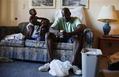 <p>Frederick Wilson, (R), peels potatoes as his nephew, Javonte Miles, 10, (C) and granddaughter Keziah Bradley, 11 months, (L), play on the couch in the motel room where the family is living in Grand Prairie, Texas July 1, 2009. REUTERS/Jessica Rinaldi</p>