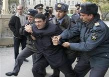 <p>Сотрудники правоохранительной службы задержали мужчину, который принимал участие в неразрешенной митинга за свободу слова, Баку 23 ноября 2006 года. Организация по безопасности и сотрудничеству в Европе (ОБСЕ) призвала власти Азербайджана прекратить практику уголовного преследования журналистов и освободить задержанных и осужденных представителей СМИ. REUTERS/Jeyhun Abdulla</p>