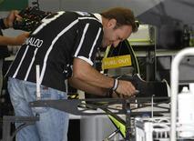 <p>O piloto Rubens Barrichello da Brawn GP verifica seu carro antes de treino para o GP de Suzuka. Barrichello afirmou que está assegurado na categoria no ano que vem.01/10/2009.REUTERS/Kim Kyung-Hoon</p>