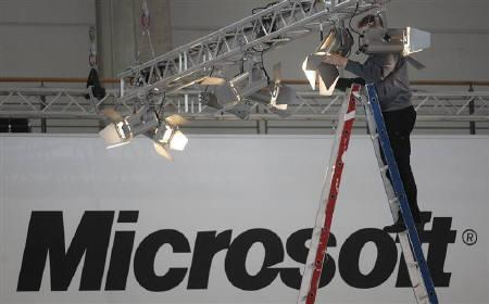A worker fix a spotlight at the Microsoft exhibit of the CeBIT fair in Hanover in this March 3, 2008 file photo. REUTERS/Hannibal Hanschke/Files