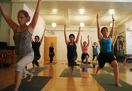 Yoga students hold a pose during an afternoon class at ''Om Factory'' yoga studio in New York, in this picture taken August 7, 2009. REUTERS/Jamie Fine