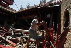 <p>A survivor cleans rubble inside a Chinese temple which was destroyed by a powerful earthquake struck in Padang of the Indonesia province October 7, 2009. REUTERS/Enny Nuraheni</p>