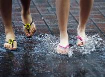<p>Two women splash their feet in a puddle during a rainstorm in Cambridge, Massachusetts July 7, 2009. REUTERS/Brian Snyder</p>
