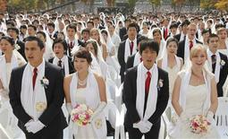 <p>Newlyweds answer the affirmation of vows during a mass wedding ceremony of the Unification Church at Sun Moon University in Asan, south of Seoul October 14, 2009. About 5,000 couples from 120 countries around the world exchanged wedding vows on Wednesday, the church said. The Unification Church founded by South Korean evangelist Reverend Moon Sun-myung in Seoul in 1954, performed its first mass wedding in 1961 with 33 couples. REUTERS/Lee Jae-Won</p>