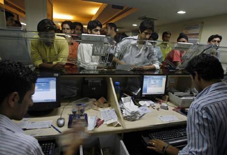 People perform transactions at a bank in Srinagar in this August 2008 file photo. Indian banks profits would be hurt after the Reserve Bank raised the provision ratio for bad debts in its credit policy review and analysts expect top two State Bank of India and ICICI Bank to be among the worst affected. REUTERS/Fayaz Kabli