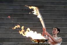 <p>A atriz grega Maria Nafpliotou acende a tocha olímpica em Atenas. REUTERS/Yiorgos Karahalis</p>