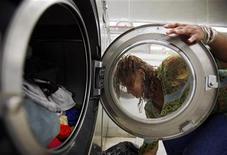 <p>Una donna carica la lavatrice. REUTERS/Brian Snyder (UNITED STATES)</p>