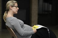 """<p>Julie Schultz, who is eight months pregnant, waits to receive a free H1N1 flu vaccine at Richard J. Daley College, as six city colleges offered the vaccine to children, the elderly, pregnant women and other """"high risk"""" people, in Chicago October 24, 2009. REUTERS/Frank Polich</p>"""