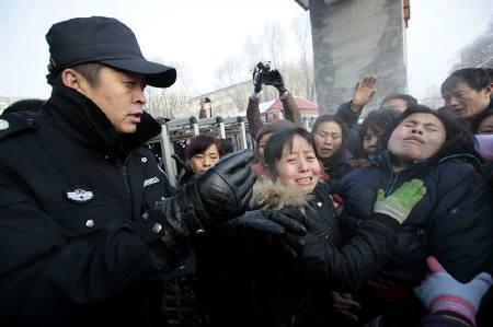 11月23日、中国の国営メディアによると、黒竜江省鶴崗市の炭鉱で21日に発生したガス爆発事故の死者は、同日までに104人となった。写真は警察ともみ合う死亡した作業員の遺族(2009年 ロイター/Aly Song )