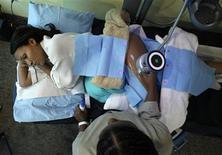 <p>Una paciente recibe un tratamiento de reducción de grasa en una clínica de belleza en Caracas, 20 nov 2009. Pese a estar golpeados por la recesión y una rampante inflación, los venezolanos no muestran señales de querer recortar el gasto en retoques faciales, liposucciones e implantes mamarios, que se han convertido en tratamientos habituales de belleza. Los tiempos difíciles incluso pueden haber impulsado los procedimientos estéticos en la medida en que la gente busca formas de darse ánimo, aún a costa de echar mano a los ahorros o de endeudarse para llegar al quirófano, dijeron cirujanos. REUTERS/Jorge Silva</p>