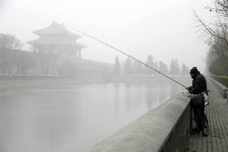 A resident fishes outside the Forbidden City during heavy fog in Beijing November 25, 2009. Three little letters could spell big trouble for global climate change negotiations even after China, the world's biggest emitter of greenhouse gases, announced its first firm goals to curb emissions. REUTERS/Jason Lee