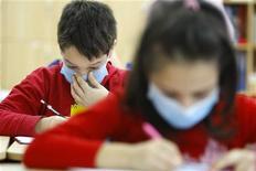 <p>Bambini in classe con la mascherina per limitare la diffusione del virus, in una scuola di Bucarest. REUTERS/Bogdan Cristel</p>