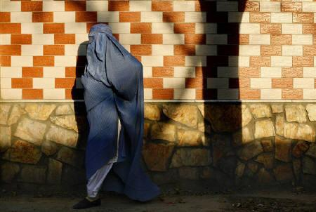 An Afghan woman in burqa walks down the street in Kabul November 16, 2009.   REUTERS/Jerry Lampen