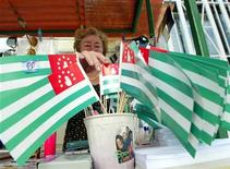 <p>Лоточница продает национальные флаги Абхазии в Сухуми 30 сентября 2009 года. Нижняя палата парламента Белоруссии провела в пятницу последнее в этом году пленарное заседание, так и не рассмотрев вопреки ожиданиям Москвы вопрос о суверенитете мятежных грузинских регионов Абхазии и Южной Осетии. REUTERS/Eduard Kornienko</p>