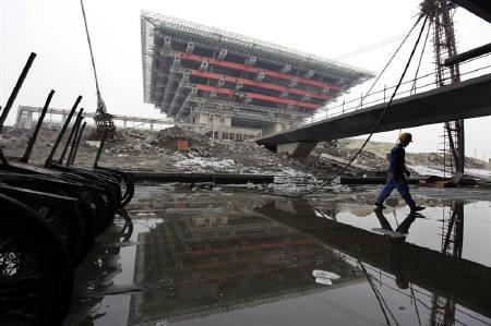 A migrant labourer walks at a construction site near the Chinese Pavilion at the Shanghai 2010 Expo site in this June 2009 file photo. REUTERS/Aly Song
