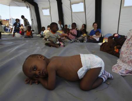 1月25日、地震被災のハイチ孤児が人身売買や不法養子縁組に巻き込まれる恐れが増大している。写真はポルトープランスの避難所で横になる孤児。20日撮影(2010年 ロイター/Wolfgang Rattay)
