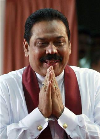 Sri Lanka's President Mahinda Rajapaksa gestures to party members at the election high commission in Colombo January 27, 2010. REUTERS/Dinuka Liyanawatte