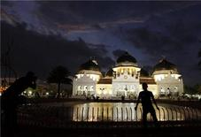 <p>An Indonesian youth takes a picture of his friend in front of the Baiturrahman mosque in Banda Aceh December 24, 2009. REUTERS/Beawiharta</p>