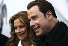 """<p>Actor John Travolta (R) and his wife Kelly Preston speak to television reporters as they arrive at the premiere of """"From Paris With Love"""" in New York January 28, 2010. REUTERS/Jessica Rinaldi</p>"""