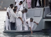 <p>Family members and friends look on as Mahatma Gandhi's granddaughter Ela Gandhi (C), great grandsons Kidar Ramgobin (2nd R) and Satish Kidar (R) scatter his ashes during a ceremony marking the anniversary of his death in the Indian Ocean at Durban January 30, 2010. REUTERS/Rogan Ward</p>