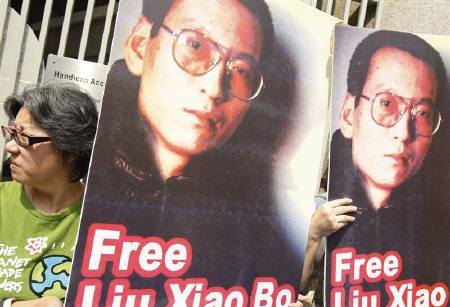 Demonstrators hold pictures of Chinese dissident Liu Xiaobo during a protest in Hong Kong October 23, 2009. China's Foreign Ministry warned on Tuesday against giving a Nobel Peace Prize to leading jailed dissident Liu Xiaobo, a nomination made by the U.S. chapter of rights group International Pen. REUTERS/Tyrone Siu/Files