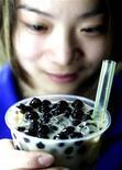 """<p>Singapore. Impiegata della catena """"Quickly"""" mostra una bevanda a base di te, frutta e tapioca. Foto d'archivio. REUTERS/STR New</p>"""