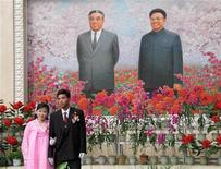 <p>Северокорейская пара позирует перед изображением скончавшегося корейского лидера Ким Ир Сена и нынешнего главы страны Ким Чен Ира на выставке цветов кимирсенхва в Пхеньяне 12 октября 2005 года. Мэрия Владивостока поддержала идею Пхеньяна украсить город цветами, выращиваемыми в Северной Корее в честь семьи вождей изолированного государства. REUTERS/Lindsay Beck</p>