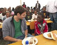 <p>Tennis player Roger Federer of Switzerland chats with a student at a school, funded by his charity, the Roger Federer Foundation, in Kore Roba February 12, 2010. Federer was in Ethiopia for a one-day visit to see the work his charity does. REUTERS/Roger Federer Foundation/Marcel Grubenmann/Handout</p>
