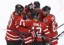 <p>Canadian Jarome Iginla (12) is congratulated by teammates after scoring against Norway during their men's hockey game at the Vancouver 2010 Winter Olympics, February 16, 2010. REUTERS/Shaun Best</p>
