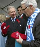<p>Britain's Prince Charles (L) wears an Olympic mitten presented to him by British Columbian Premier Gordon Campbell during a visit to the Athlete's Village in Vancouver, British Columbia November 7, 2009. REUTERS/Andy Clark</p>