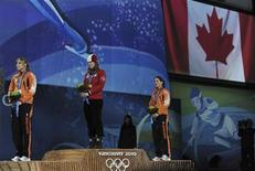 <p>Gold medallist Christine Nesbitt (C) of Canada stands with silver medallist Annette Gerritsen (L) and bronze medallist Laurine van Riessen of the Netherlands as her national anthem is played during the medal ceremony for the women's 1000 metres speed skating competition at the Vancouver 2010 Winter Olympics, February 18, 2010. REUTERS/Dylan Martinez</p>