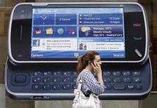 <p>Una donna al telefono davanti ad una pubblicità Nokia a Londra. REUTERS/Luke MacGregor (BRITAIN BUSINESS)</p>