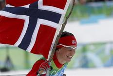 <p>Norway's Marit Bjoergen skis with national flag as she celebrates her team's victory in women's 4x5 kilometres relay classic/free cross-country skiing final event at the Vancouver 2010 Winter Olympics in Whistler, British Columbia, February 25, 2010. REUTERS/Issei Kato</p>