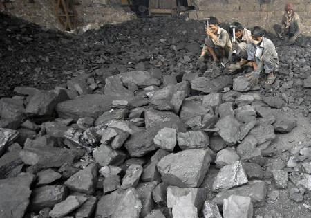 Labourers break coal to be used in a steel factory in Ellikatta village, 60 km (37 miles) from the southern Indian city of Hyderabad September 2, 2009. REUTERS/Krishnendu Halder/Files